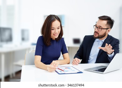Two employees discussing document at meeting