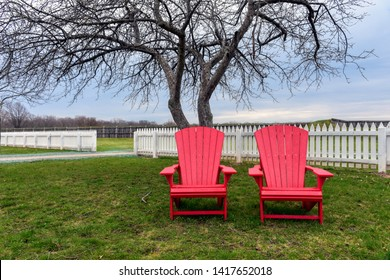 Two empty Adirondack chairs sit in front of a long white picket fence at historic Fort George, Niagara on the Lake, Ontario.  Autumn is a quiet time in the region.