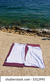 Two empty beach towels on the beach