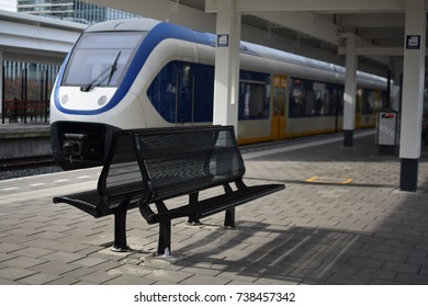 Two empty benches at a Dutch train station with the train in the background