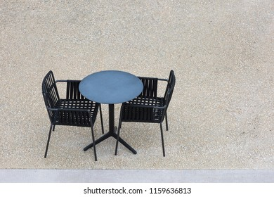 Two empty black chairs and a table on concrete from above