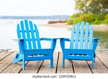 Two empty blue adirondak chairs on wooden pier by lake in summer