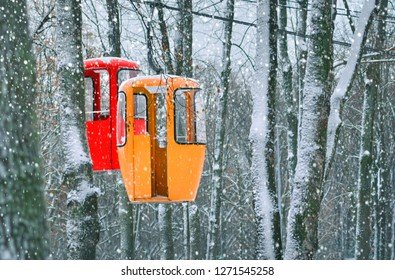 Two empty cableway cabines on a winter forest backdrop. Travel background. Funicular.
