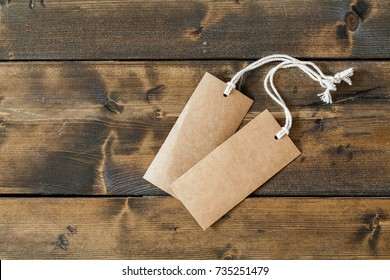 Two empty cardboard tags ready for text or other concept, laying on a wooden floor