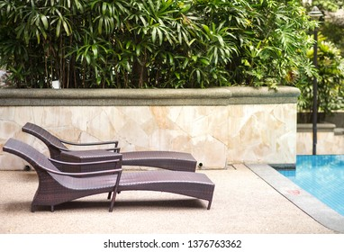 two empty chaise lounges near pool and tropic palms
