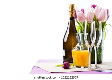 Two empty champagne flutes and a bottle of sparkling wine with tulips on background