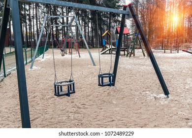 two empty children swings on playground