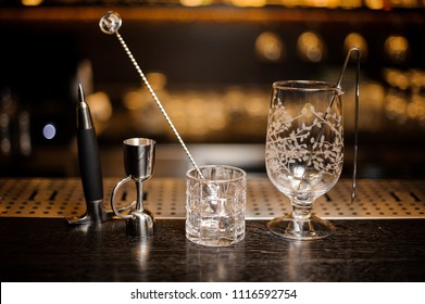 Two empty cocktail glasses and professional bar equipment arranged on the bar counter against blurred background
