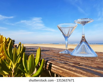 Two empty cocktail glasses stand on the table, one of which is turned upside down on a background of sand and sea on a sunny day.