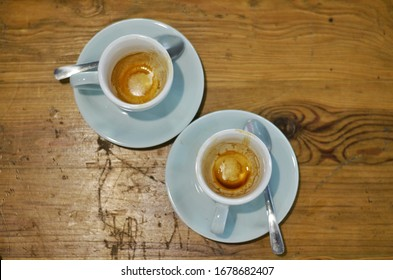 Two empty coffee cup with brown espresso stains inside, photographed flat lay on a wooden table.