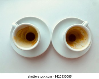 two empty coffee espresso cups with stain left in the cups on the white table in the restaurant in summer time