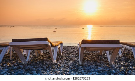 Two empty deckchairs on the evening sea coast against the background of beautiful golden sunset reflected  in the calm water