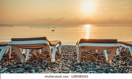 Two empty deckchairs on the morning sea coast against the background of beautiful golden sunrise reflected  in the calm water