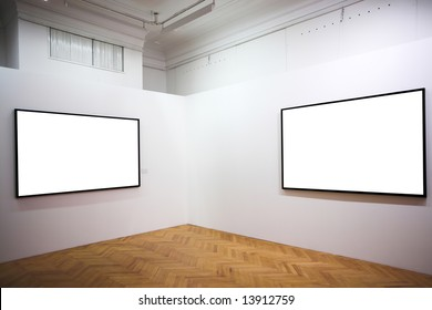 Two empty frames on white wall in museum