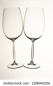 Two empty glass cups lying horizontally. Isolated white background.