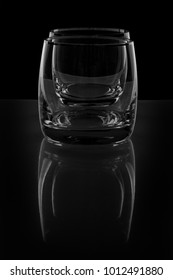 Two empty glass on black background with reflection