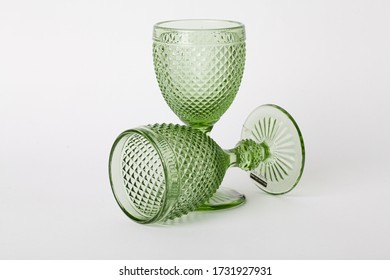 two empty glasses of green glass on a stem on a white background. close view