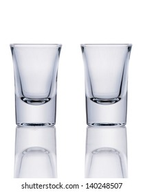Two empty glasses on a reflective surface on white background