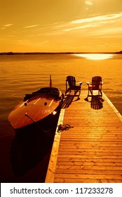 Two empty lounge chairs on dock with anchored vintage motor boat