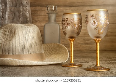 two empty luxuary wine glasses with fashion men hat and empty wine bottle on table