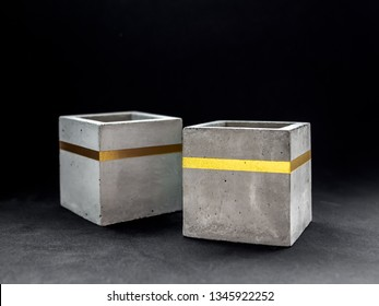 Two empty modern cubic concrete planters with gold color bar flowers on dark background. Painted concrete pot for home decoration.