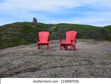 two empty red adirondack chair on the edge of a cliff with a tower on top of a lush green hill in the background, Signal Hill St John's Newfoundland Canada