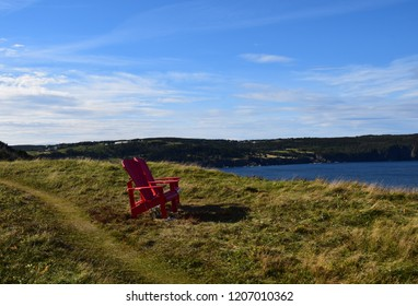 two empty red Adirondack chairs on the edge of a cliff overlooking the ocean and coastline, Silver Mine Head Path Torbay Newfoundland Canada