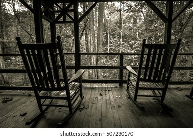 Two Empty Rocking Chairs. Two wooden rocking chairs on an old front porch. Shot in black and white with horizontal orientation.