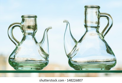 two empty rustic crystal oilcans on crystal shelf