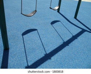 Two empty swing at the playground with a blue background
