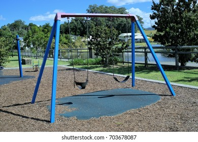 Two empty swings in park attached to metal posts with metal chains. Rubber and Fragments of wood is laid as surface of the park.