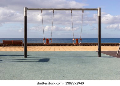 Two empty swings in playground with ocean in the background. These are metal swings for toddlers. The swing can hold a toddler from falling out