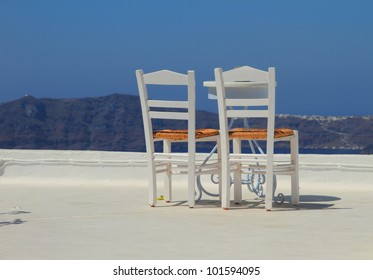 Two empty white chairs against mountains and the sky