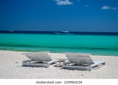 Two Empty White Chairs on Boracay Beach, Philippines Facing the Ocean