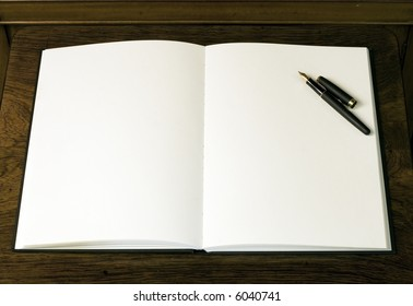 Two empty white pages and pen in book or notepad