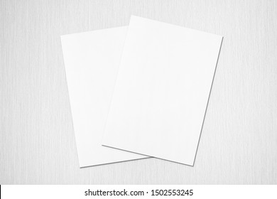 Two empty white rectangle poster or card mockups lying diagonally on top of each other with soft shadows on neutral light grey textured background. Flat lay, top view