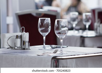 Two empty wine glasses arranged on a table in an open air restaurant or bar.