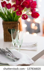 Two empty wine glasses on a table and a bouquet of flowers in daylight
