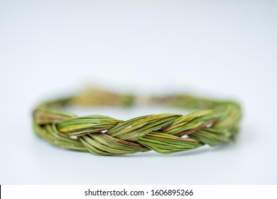 Two ends of a sweetgrass braid tied into a circle with hemp twine on a white background