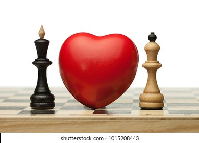 Two enemies fall in love. There is the red heart between black chess queen and white king  on the chess board. Isolated. Forbidden love.