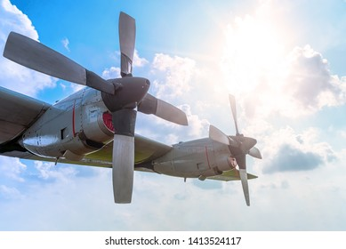 Two Engine Aircraft Propeller of Turboprop Airplane Flying High in Cloudy Sky with Sun Shine Brightly.