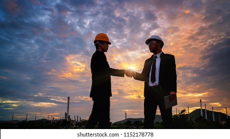 two engineer oil industry closing a deal in front of oil refinery at sunset time,Business partnership meeting concept.