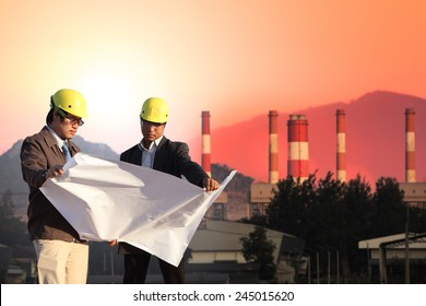two engineer on Power plant and electric lines with sunset time and mountain background