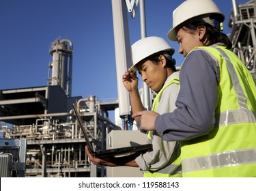two engineer power and energy discussion on location site using laptop