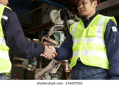 Two engineer shaking their hands at a manufacturing area