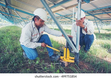 two engineer working on checking and maintenance equipment at green energy solar power plant: Wrench tightening at solar mounting structure