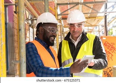 Dwóch inżynierów, Afroamerykanin i kaukaska, w pomarańczowych i żółtych kurtkach ochronnych i kaskach, pracujących z tabletem wśród rusztowań na placu budowy