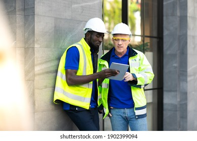 Two engineers African american engineer and caucasian electrician wearing white hard hat walk in new building holding solar panel on hand and Discuss Work
