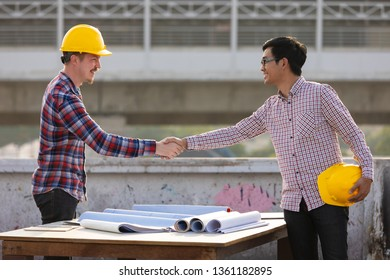 Two engineers, Asian and Caucasian shaking hands after work is finished on rooftop of construction site with beautiful sunlights in background.