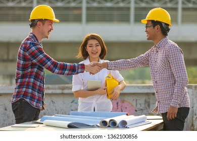 Two engineers, Asian and Caucasian shaking hands after work is finished on rooftop of construction site with female in team looking and smiling with happiness.